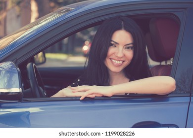 Charming stylish woman sitting in a new modern car smiling at camera happily