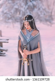 charming sweet dark-haired girl with closed eyes reads prayer to gods of war before terrible fight, elegant princess holds silver sword, meditation with weapon for hardening spirit of warrior