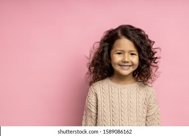 Charming sweet little model on pink background. Close up of curly dark haired girl 5 years old, wearing beige sweater, smiling broadly with teeth, looking at camera with happy expression. Copy space.
