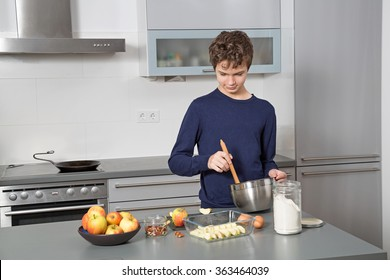 Charming teenage boy in the kitchen baking an apple pie