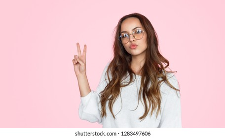 Charming teenager in glasses pouting lips flirty while holding hand with two fingers gesture