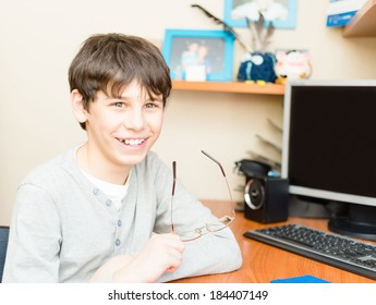 charming teenager sitting at a computer desk