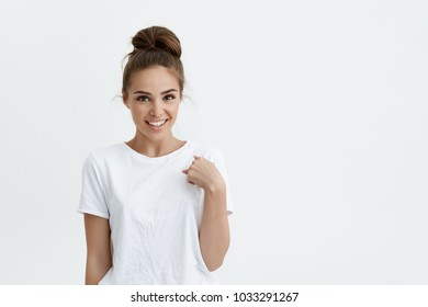 Charming tender caucasian woman with bun hairstyle standin over white background and pointing at herself, expressing surprise and disbelief. Girl can not believe that friend fell in love with her