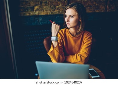 Charming thoughtful hipster girl with modern smartwatch on hand looking out of window and thinking on creative ideas for developing own training project sitting at computer in coffee shop