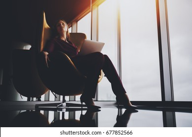 Charming tired lady sprawling out on elegant yellow armchair in luxury office after difficult work meeting, beautiful caucasian businesswoman chilling after hard day and online conversation via laptop