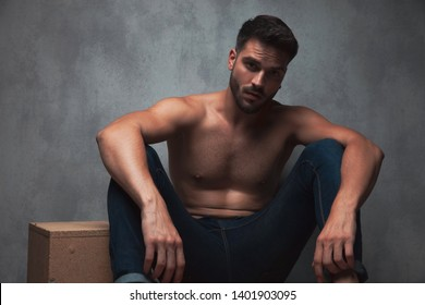 Charming topless guy romantically staring to the camera and resting his arms on his knees while sitting on gray studio background