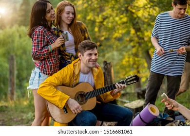 charming tow female friends hugging while standing behind the boy with guitar, close up photo. friendship, pleasant pastime