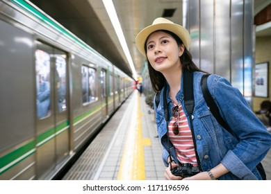 charming travle female waiting for her train coming and holding her camera with a cheerful look.