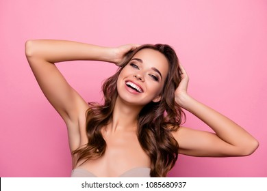 Charming, trendy, glad, dreamy, lovely, brunet coquette holding hands on head, touching her perfect curly hair, isolated on pink background