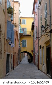 A charming view of a small street in Villefranche-sur-Mer, France, with colorful buildings and a yellow three-story house with an archway in the middle of the path.