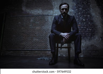 Charming villain sitting in dark room