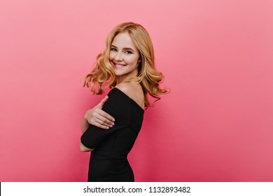 Charming white lady enjoying photoshoot. Enthusiastic smiling girl standing with arms crossed on pink background.