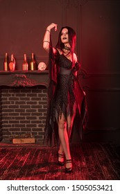 Charming witch in a dark room on Halloween