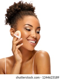 Charming woman applying powder on her face with cosmetic application. Photo of african american woman with healthy skin on white background. Youth and skin care concept