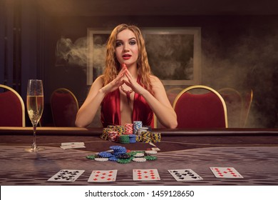 Charming woman with a beautiful hairstyle and perfect make-up is playing poker. Casino.