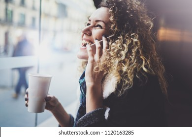 Charming woman with beautiful smile using mobile phone during rest in coffee shop. Blurred background