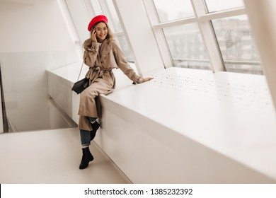 Charming woman in beige long coat and red stylish beret sits on windowsill. Portrait of lady in glasses with crossbody bag posing by window