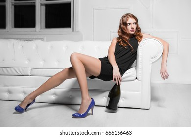 Charming woman in black dress and blue shoes posing with bottle on the sofa