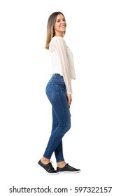 Charming woman in braided shirt and jeans laughing at camera. Side view. Full body length portrait isolated over white background.