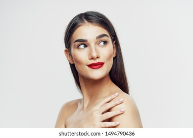 A charming woman with bright makeup and bare shoulders looks away from the side