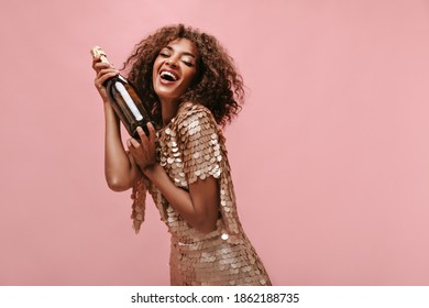 Charming woman with brunette curly hairstyle in shiny stylish dress laughing and holding bottle with wine on isolated backdrop..
