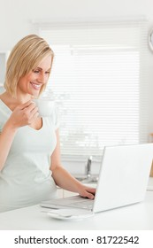 Charming woman with a cup of coffee and a laptop in the kitchen