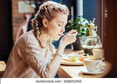 Charming woman with cute hairstyle having lunch during the rest in coffee shop, happy Caucasian female eating breakfast while relaxing in cafe during free time