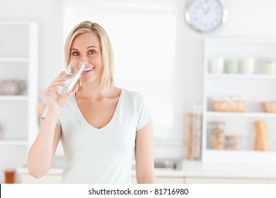 Charming woman drinking water while standing looks into camera in the kitchen