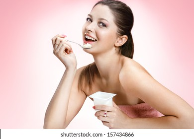 Charming woman eating yogurt / studio photography of brown-eyed brunette girl holding spoon and a container of yogurt - on blurred background