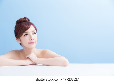 charming woman face smile and look somewhere close up while lying isolated on blue background, asian girl