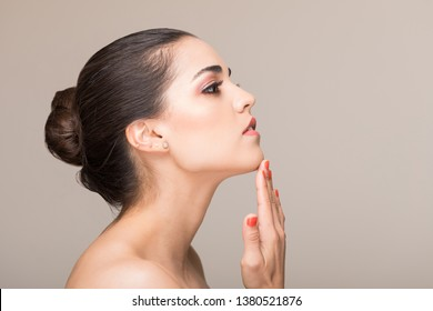 Charming woman with flawless face touching her chin in studio