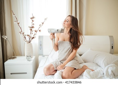 Charming woman with hairdryier sitting on the bed at home