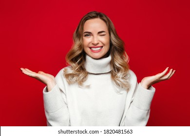 Charming woman with happy surprise on her face spreading her hands to the side, smiling and winking, wear white sweater, isolated on red background, copy space. Winter season and sale