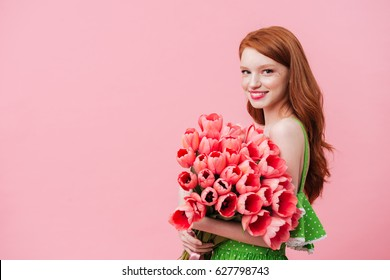 Charming woman holding big bouquet of pink tulips isolated