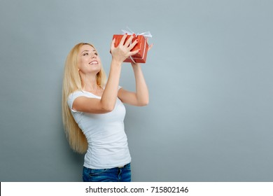 Charming woman holding red box with present