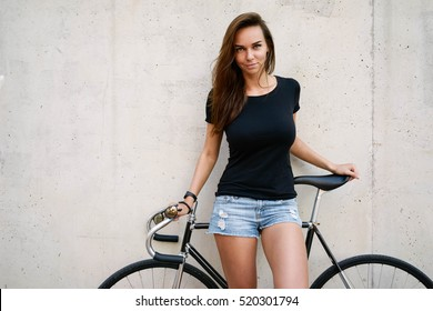A charming woman with long brown hair wearing a blank black t-shirt is standing on a concrete wall background on a street. Empty space for text or design.