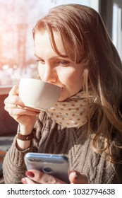 Charming woman with phone in cafe. Bright sunny morning in cafe