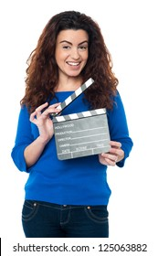 Charming woman posing with clapperboard in hands. All on white background.