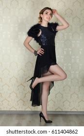 Charming woman posing in elegant black dress on neutral background
