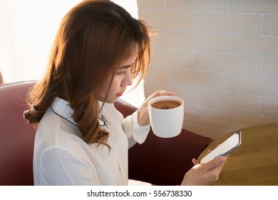 Charming woman reading and looking her smartphone, one hand hold coffee cup and sitting at coffee shop cafe. Beautiful woman is feeling chilling