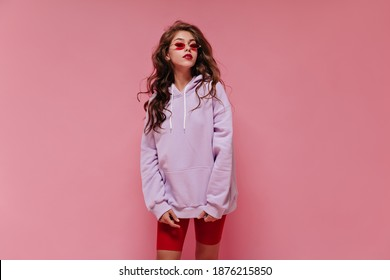 Charming woman in red cycling shorts and purple hoodie poses on pink background. Young girl in sunglasses looks into camera on isolated.