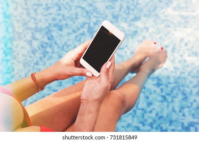Charming woman in red swimming suit sitting on side of pool using smartphone in sunlight