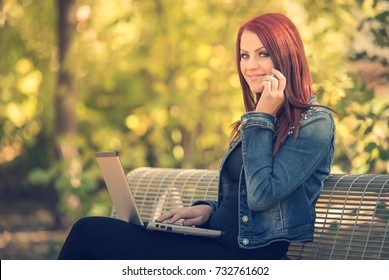 Charming woman sitting in the park and call someone with her phone