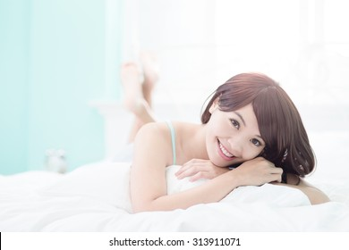 Charming woman Smile face close up and she lying on the bed in the morning , asian girl