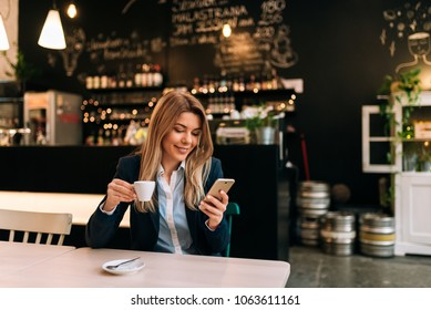 Charming woman using phone while holding a cup of coffee.