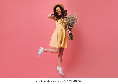Charming woman in yellow dress jumps on pink background and holds bouquet. Funny girl in converse and straw hat posing with flowers in her hands