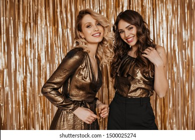 Charming women in smart outfits are smiling and looking at camera against golden background