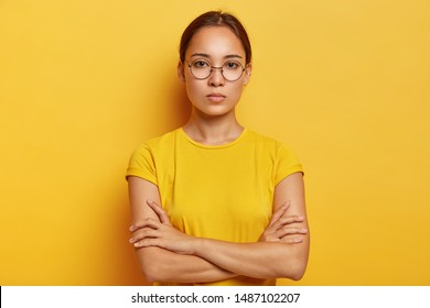 Charming young Asian woman has fresh skin, looks at camera confidently, has serious expression, keeps hands crossed over chest, wears optical glasses and yellow t shirt, being deep in thoughts