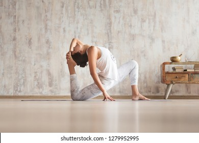 Charming young beautiful woman yoga instructor doing yoga asana for back and leg joints standing on the floor against the background of a concrete wall and vintage console