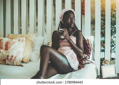 A charming young black woman has just woken up and drinking morning coffee from the cup in her hands while staying in the bed in her nightie and pensively looking aside; wooden stripes in a background
